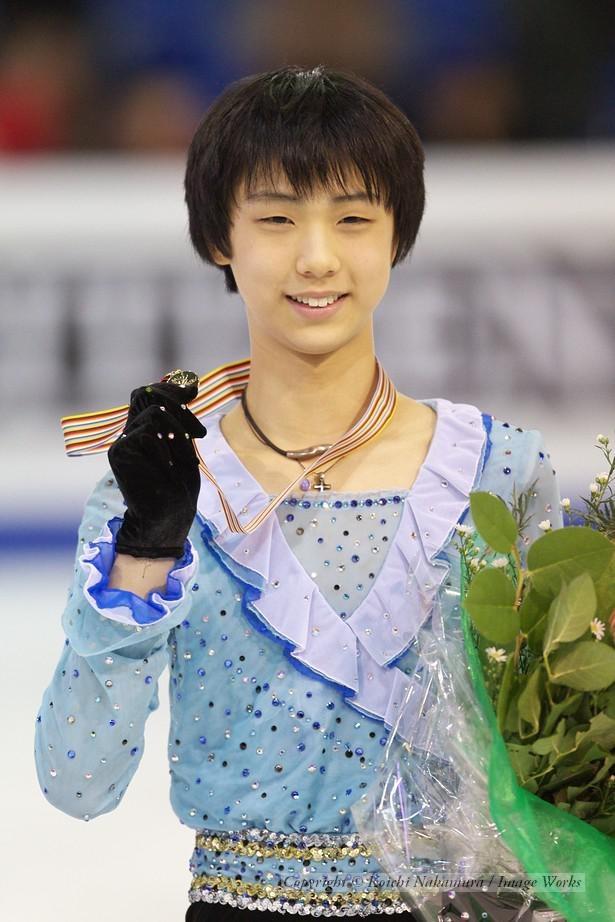 表彰式でメダルを掲げる羽生結弦