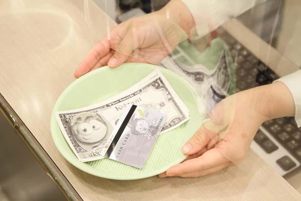 キッゾや現金のやり取りは、直接触れないようトレーを使用 ※画像はイメージ/キッザニア甲子園