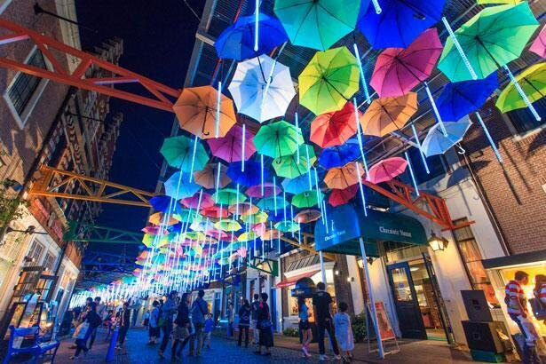 空を埋め尽くす無数のカラフルな傘から光が降り注ぐ「光のアンブレラストリート」