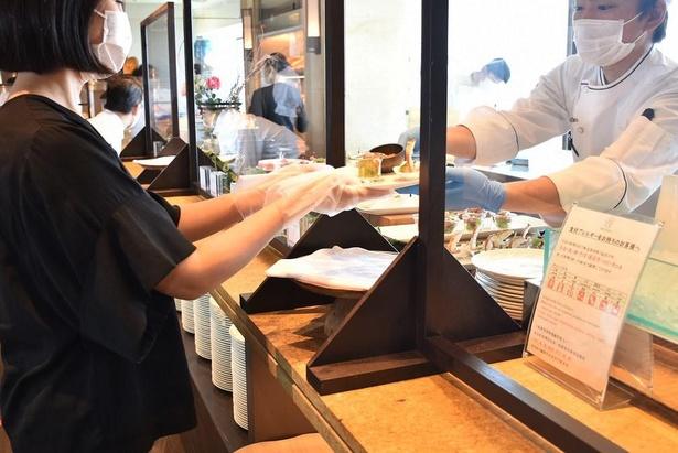 高いシールドを設置し飛沫感染を防止。受取る際のビニール手袋も用意されている(神戸ポートピアホテル)