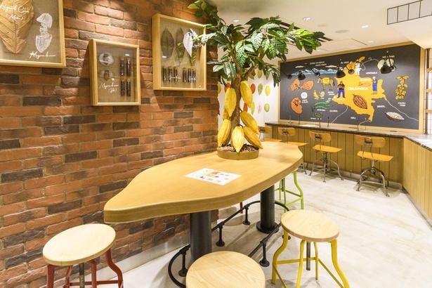 コロンビア産カカオの情報ボードがカウンター前に掲げられている。カカオ豆型のテーブルがかわいい店内