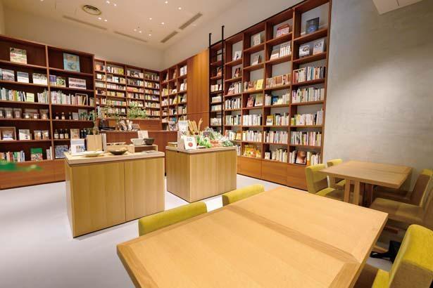 テーブル席と「鴎来堂」の選書が並ぶ書店、「坂ノ途中」の物販スペースが共存/本と野菜OyOy