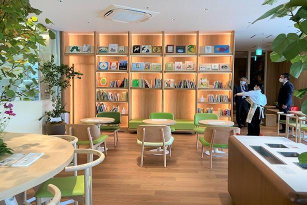 たくさんの観葉植物が配置された、ナチュラルな雰囲気のカフェスペース。絵本が並ぶ「えほん棚」も大きな魅力