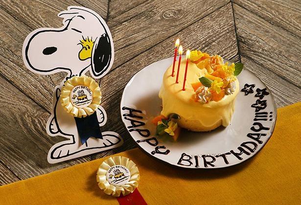 ウッドストックをモチーフにした黄色いケーキ。写真左のバースデープランのロゼットは主役だけがもらえる特別なもの