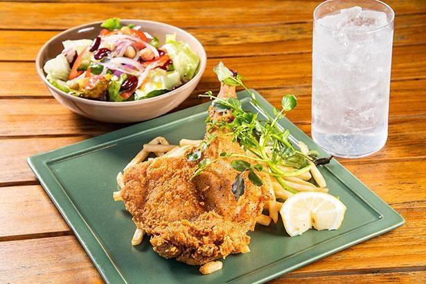 平日ランチで食べられる骨付きフライドチキン(1,300円・税抜き)。ランチドリンク&サラダ付き。ナンバーエイト・ジントニック(写真右)はランチに+400円で味わえる
