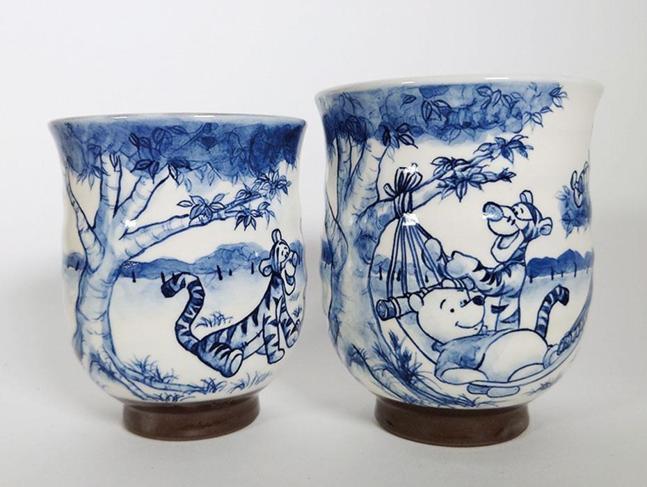 """京清水焼の朝日堂は、くまのプーさんが描かれた組湯呑(1万4000円)やミッキーマウス、ミニーマウスが描かれたマグカップ(9000円)、ディズニープリンセスの飾り皿(意匠監修中)などを出展。いずれも手描きのぬくもりを感じる作品 (C)  DISNEY Based on the """"Winnie the Pooh"""" works by A.A. Milne and E.H. Shepard."""