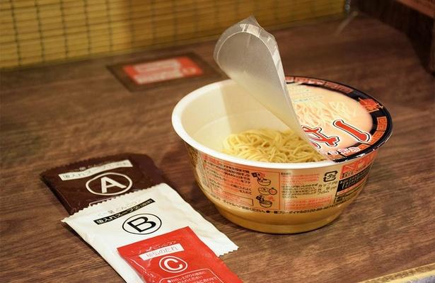 ふたを開けると液体スープ、粉末スープ、赤い秘伝のたれが入っている