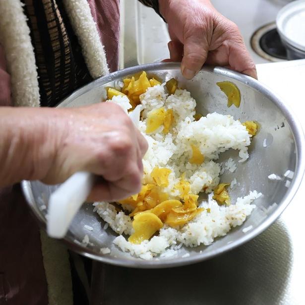 ご飯につぼ漬をまぶしていく。ご飯が全体的に黄色くなるほどにどっさり