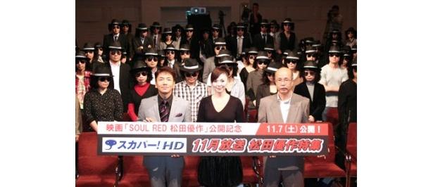 松田優作の仮装をしたファンと記念撮影した、くりぃむしちゅー・上田晋也、松田美由紀、丸山昇一(左から)