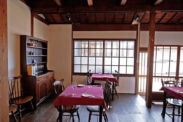 赤いクロスが敷かれたアンティーク風のテーブルを、空間を贅沢に使ってレイアウト/Ruelle