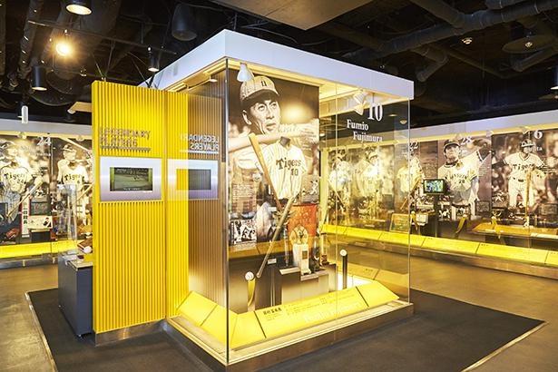 「ヒーロー列伝」藤村富美男、村山 実、吉田義男ら、阪神タイガースの永久欠番選手を筆頭に、球団設立から現代までの歴代名選手の映像や展示品が並ぶ