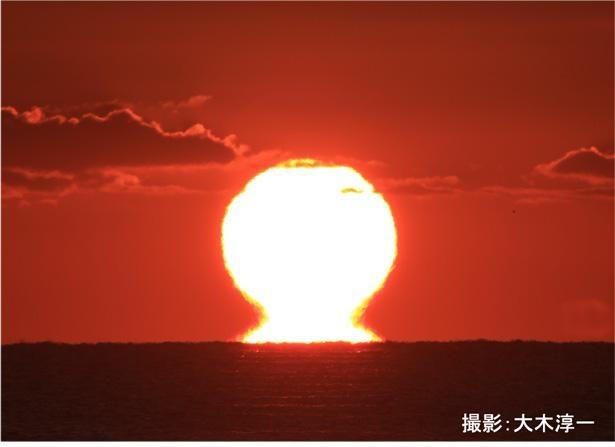 """水平線に接した太陽が、まるでだるまのようにくびれて見える""""だるま太陽"""""""