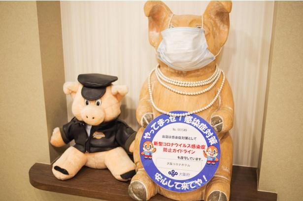 藤井さんの初投稿は館内のブタちゃん紹介のコーナー。その初投稿で登場した「ブタに真珠ブタちゃん」(写真右)もコロナ対策バッチリ