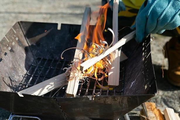 細かく割ったまきを並べて火種を入れると、フェザースティックを中心に火が広がっていく