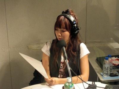 ラジオ生放送中。リスナーからのメッセージを楽しそうに読み上げる