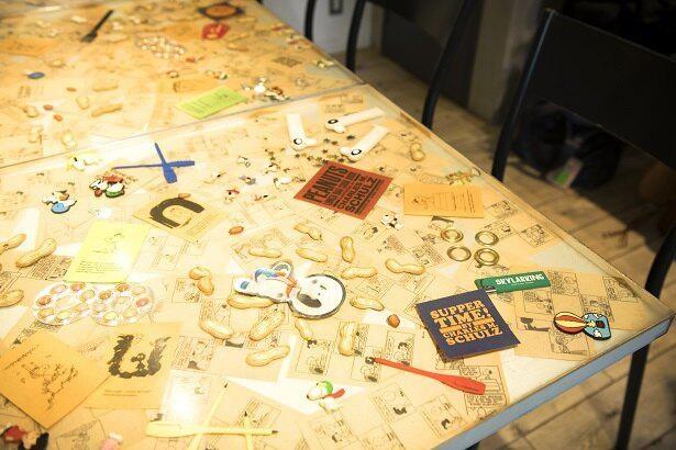 """【写真】中目黒にある「ピーナッツカフェ」の店内。スヌーピーのトイと一緒に、""""ピーナッツ""""や雑貨が埋め込まれたテーブルがかわいい!"""