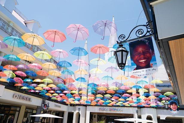 今回の新設エリア。カラフルな傘を見上げれば、気分も晴れ晴れ。笑顔のフラッグにも注目を!