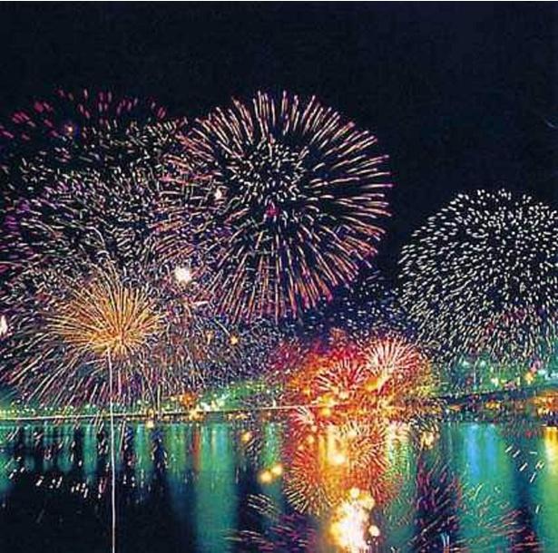 沖合に浮かぶ2隻の舟から打ち上げる花火が、海面に映えて美しい