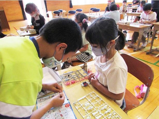 """【画像】ガンプラの特別授業では、上級生が下級生にガンプラの作り方をレクチャーする場面も。こうした""""教え合い""""""""助け合い""""が各所で見られたという"""