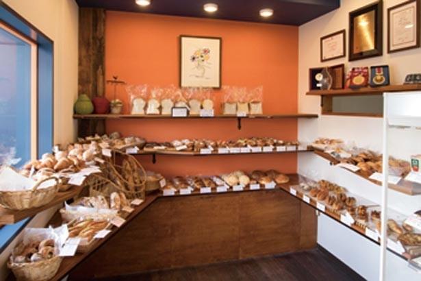 オレンジ色の内装に、焼き色の美しいパンが映える。壁には数々の受賞経歴を掲示/Boulangerie Yamazaki