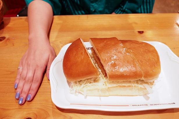 「エビカツパン」880~950円。手と比較しても分かるとおり、両手で持ち上げなければ食べられないサイズの大きさ