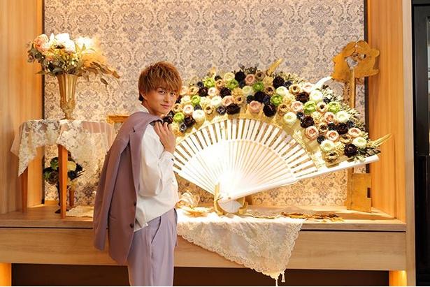 大きな扇子の前でポーズを決める小林さん。小さくなった体でベルサイユ宮殿を冒険するアリスの気分!