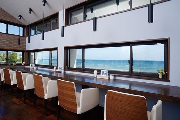 天井が高く、ゆったりくつろげる雰囲気。2階のカウンター席は砂浜や海を一望できる/Cafe KURUMA28