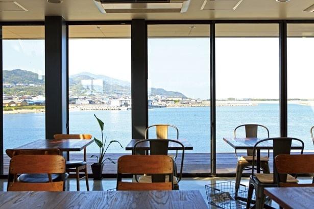 店内からは、一面の大きな窓のすぐ向こうに、陽射しをキラキラと反射する穏やかな生穂漁港が見える/PASTA FRESCA DAN-MEN