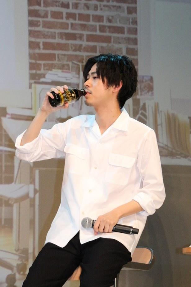【写真を見る】豪快に「クラフト ボス」を飲む成田は、「おいしいです!」とニッコリ