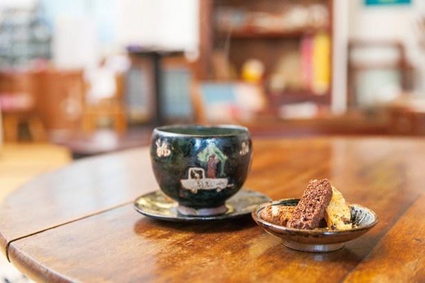 【写真を見る】抹茶オレ(600円)は益子焼作家、寺門広気さんが手がけた器。特製のビスコッティ(200円)と共に