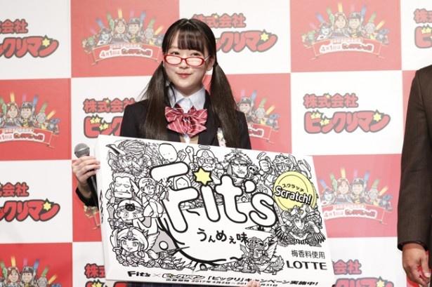 【写真を見る】「しろいフィッツ」の巨大ボードを掲げる越智ゆらのさん