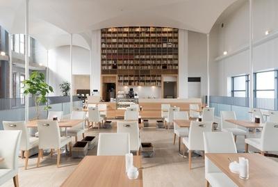 明るい光があふれる2Fのカフェには天井まで届く巨大な本棚を設置