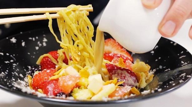 【写真を見る】フルーツなどの具材の上に豚骨スープをかけて