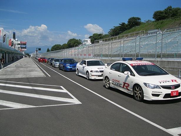 オフィシャルカーを先頭にピットレーンに並ぶ参加車両たち