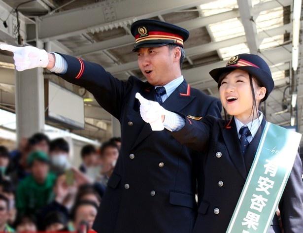 【写真を見る】有安杏果が本職の駅長と共に「出発信号!」と合図