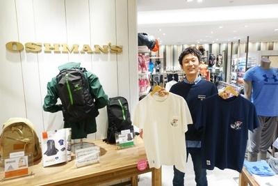 「OSHMAN'S」スタッフの海野さん。手にはシャチホコをデザインした「CHUMS」の「オリジナルTシャツ」(白・ネイビー各4212円)