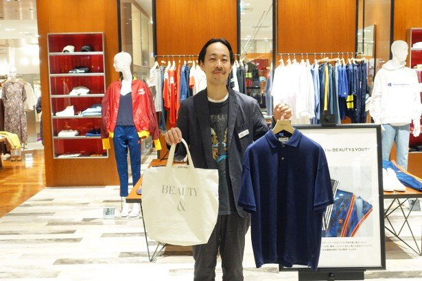 「BEAUTY&YOUTH UNITED ARROWS」店長の大須賀さん。右手には税抜5000円以上の買い物でもらえる「トートバック」を