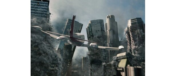 崩れゆくビル群の中を飛行機が飛び去っていく