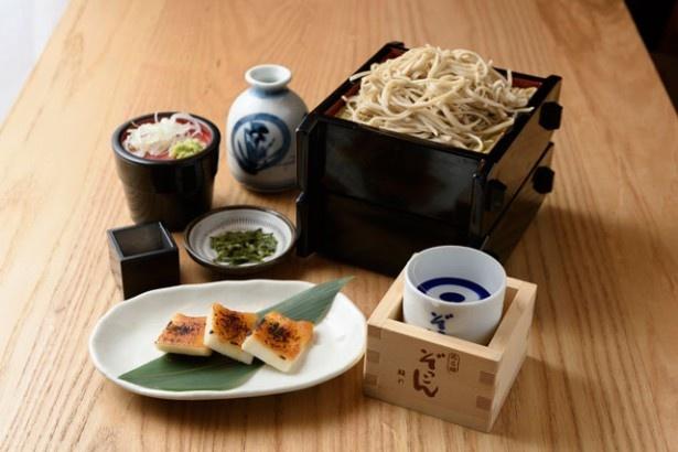 【写真を見る】「ぬる燗ぞっこん離れ」(B1階)の「周年セット」(1280円)は、大豆チーズ西京漬け焼、そば2段、日本酒が楽しめる
