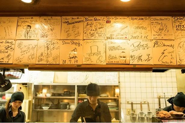 カウンター上や壁一面に訪れた著名人のサインが飾られている