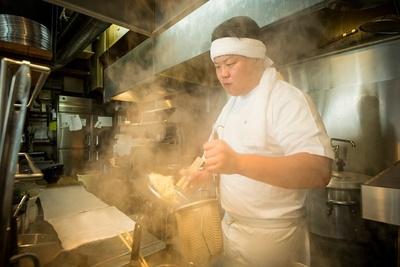 店主の山田晶仁。清潔感のある真っ白いユニフォームで、ラーメン作りに真摯に取り組む