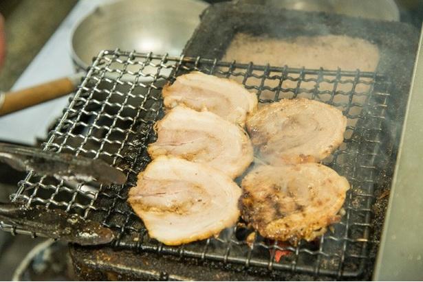 カウンター目の前の焼き台で、豚バラチャーシューを炭火で炙る。香ばしい煙も食欲をそそる