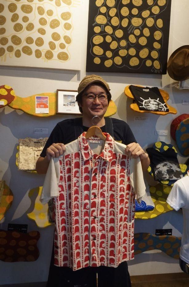 赤瓦柄のシャツを持ちながらデザインについて語る池城さん。穏やかな口調の中にも石垣島への熱い思いが伝わってくる