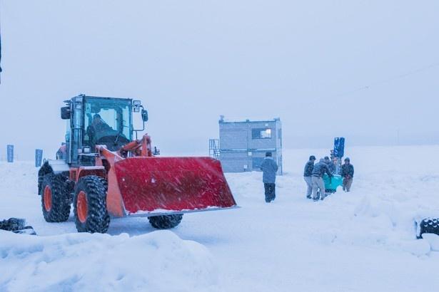 雪が舞い降る中、重機などを使ってコースを整備