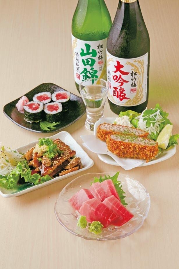 「中とろ刺身」(手前・450円)は角が立っているのが新鮮な証拠。「まぐろカツ」(中右・350円)、「すき身のカルビ焼き」(中左・250円)など。日本酒は720mlで1800円/天神橋 まぐろや