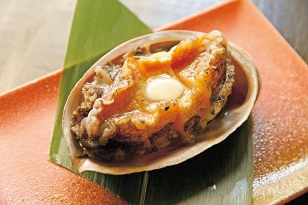 「アワビ踊り焼き」(730円)。生けすから出してすぐ焼き上げるので食感はプリップリ!やみつきになること間違いなし/産直鮮魚と天ぷら 立ち呑み あたりや食堂 なんば店