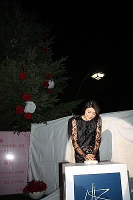 クリスマスツリーの点灯ボタンを押す山田優さん