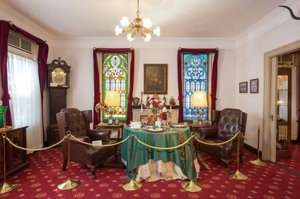 【写真を見る】光が射し込むステンドグラスが美しい1階の食堂。食卓には季節の花が/うろこの家・うろこ美術館