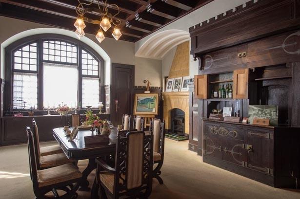 中世城館風の様式美を取り入れた1階食堂。暖炉飾りや飾り扉などの見事な意匠に圧倒される/風見鶏の館