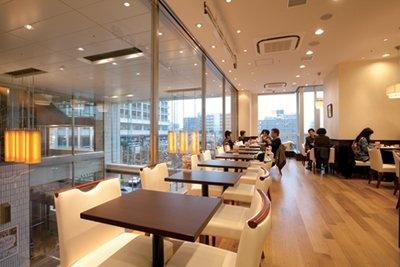 ショップ内の階段を上がると、ガラス張りのカフェが広がる (Sandog Inn 神戸屋 東神奈川駅店)